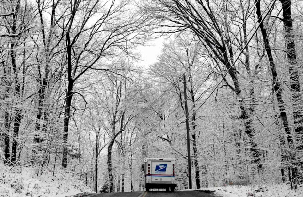 A U.S. Mail delivery truck drives beneath snow covered trees along Clausland Mountain Road in the New York City suburb of Orangeburg, New York